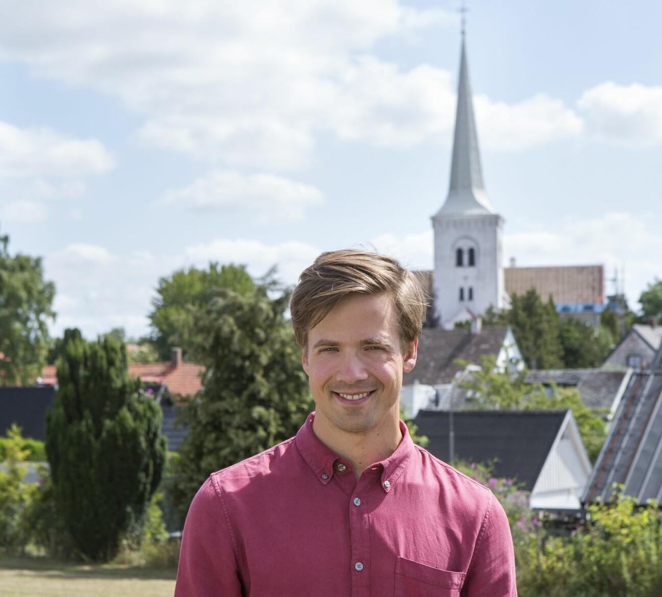 Nils Holmqvist i vinröd skjorta och leende framför Anderslövs vitkalkade kyrka.
