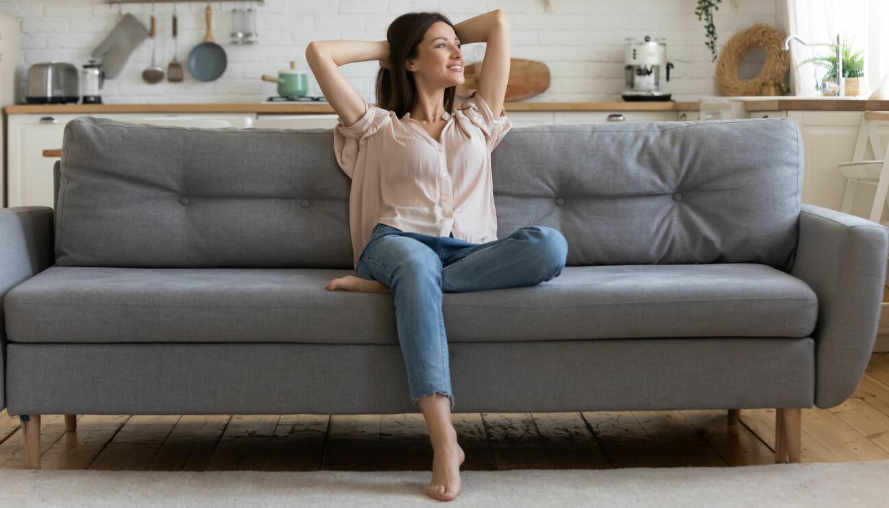 Nöjd kvinna sitter i en soffa