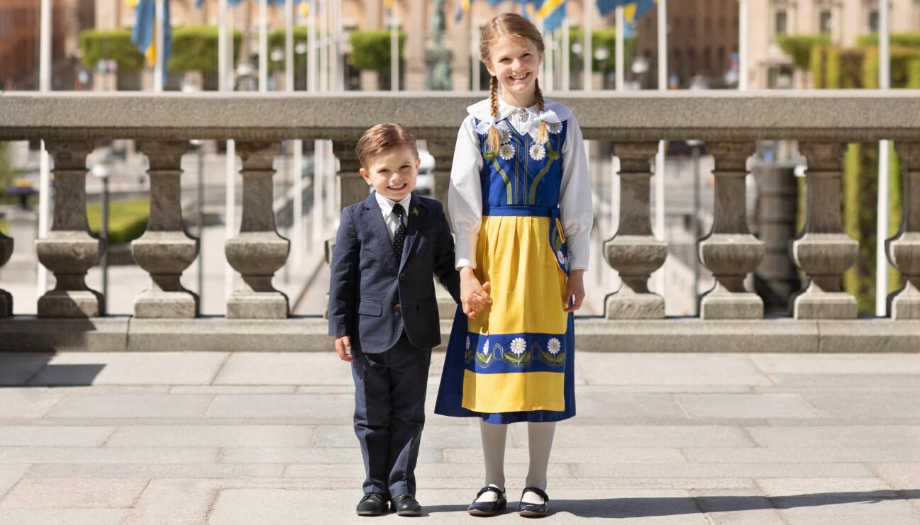 Prinsessan Estelle och prins Oscar håller varandra i handen iklädda Sverigedräkt och kostym på nationaldagen den 6 juni 2020.