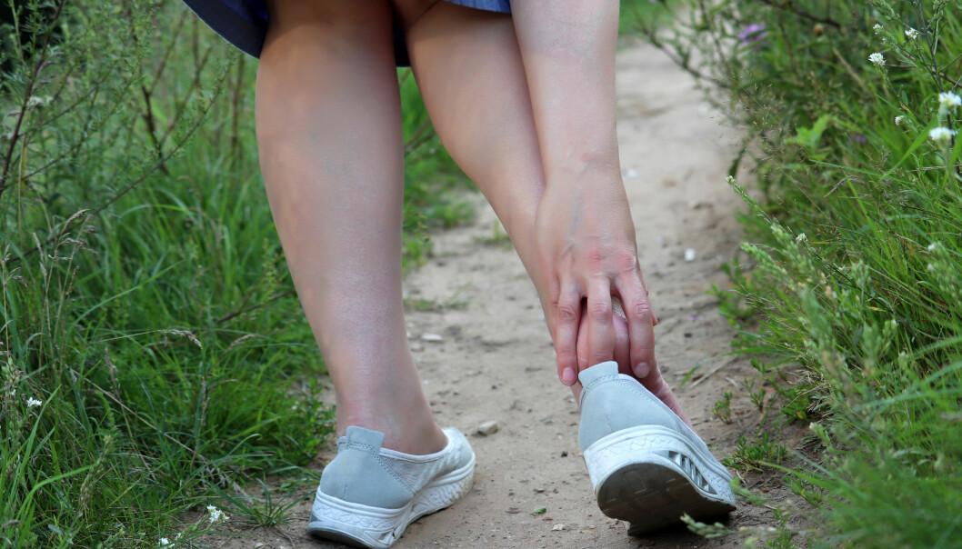 Ont under fötterna kan bero på hälsporre. Här tar sig en kvinna om hälen av smärta.