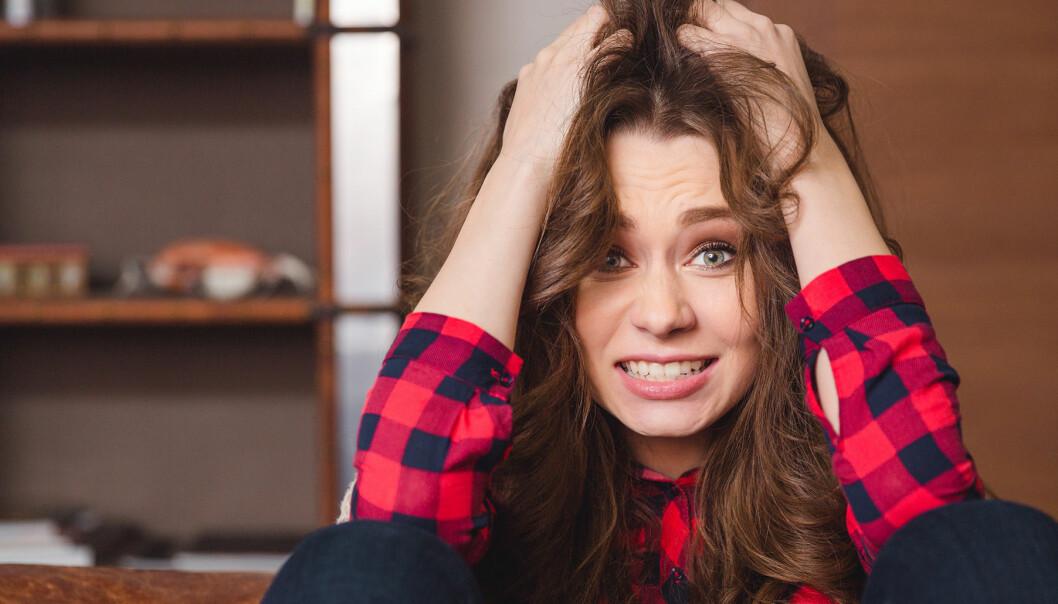 Kvinna river sig I håret och ser uppgiven ut