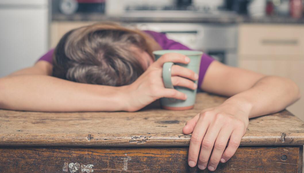 Utmattad kvinna hänger över ett köksbord