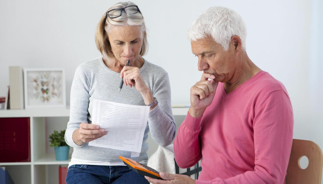 Bekymrat par i dryga 50-årsåldern sitter med pappersarbete och räkneapparat.