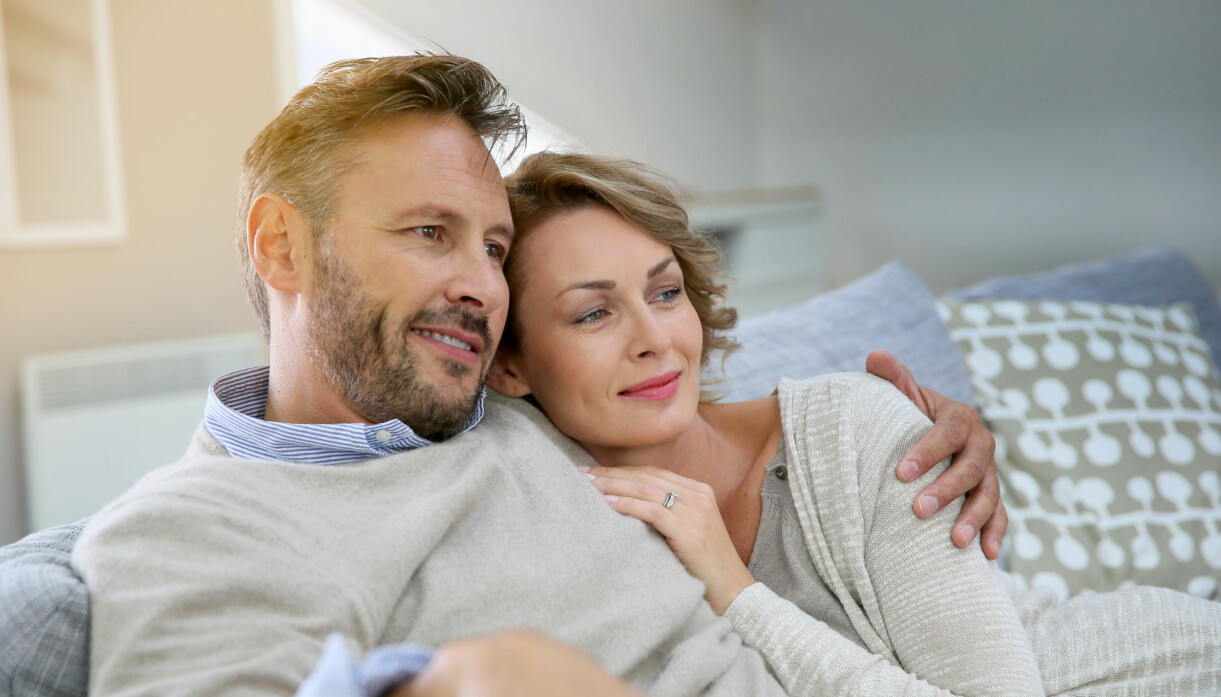 Par i 35-40-årsåldern sitter tätt ihop i soffan och ser lyckliga ut.
