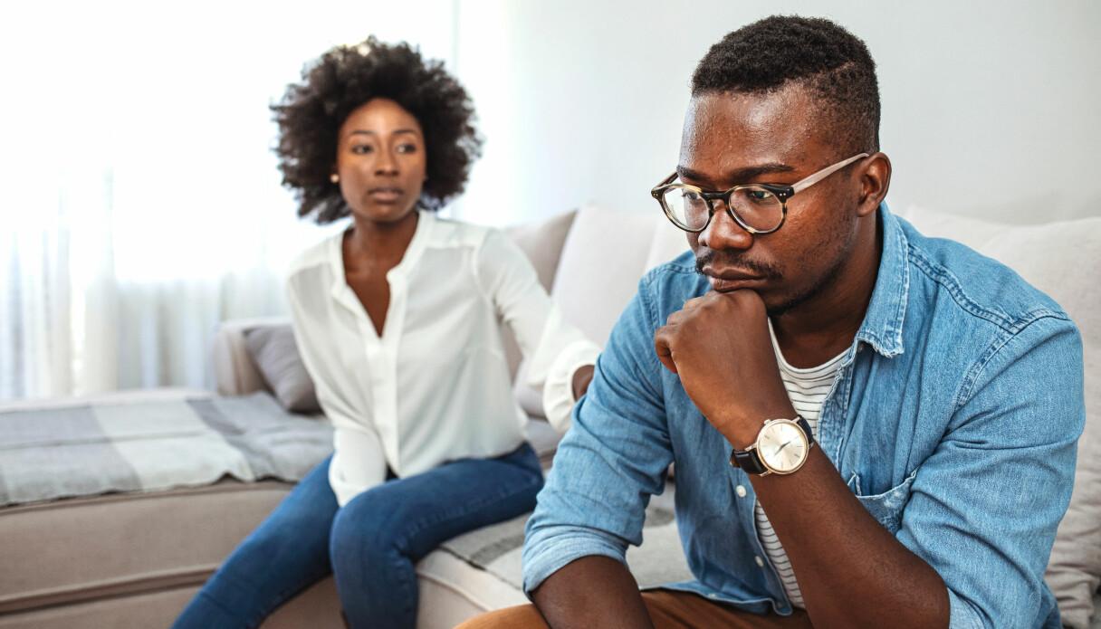 Ett par som sitter i en soffa och har precis bråkat om den ena partnerns ex.