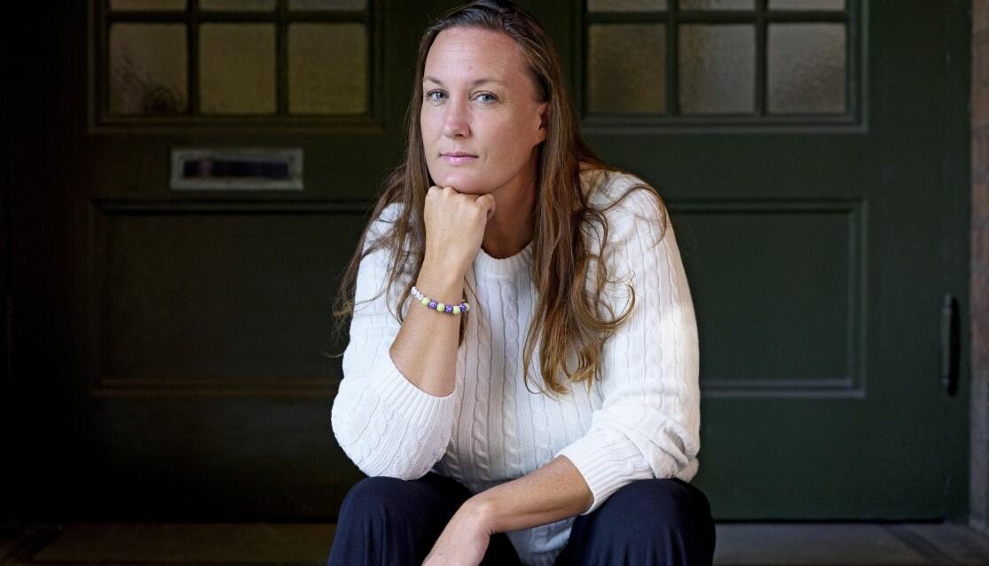 Paulina Bengtsson sitter framför en dörrport och vilar hakan på sin slutna hand. Hon ser rakt in i kameran.