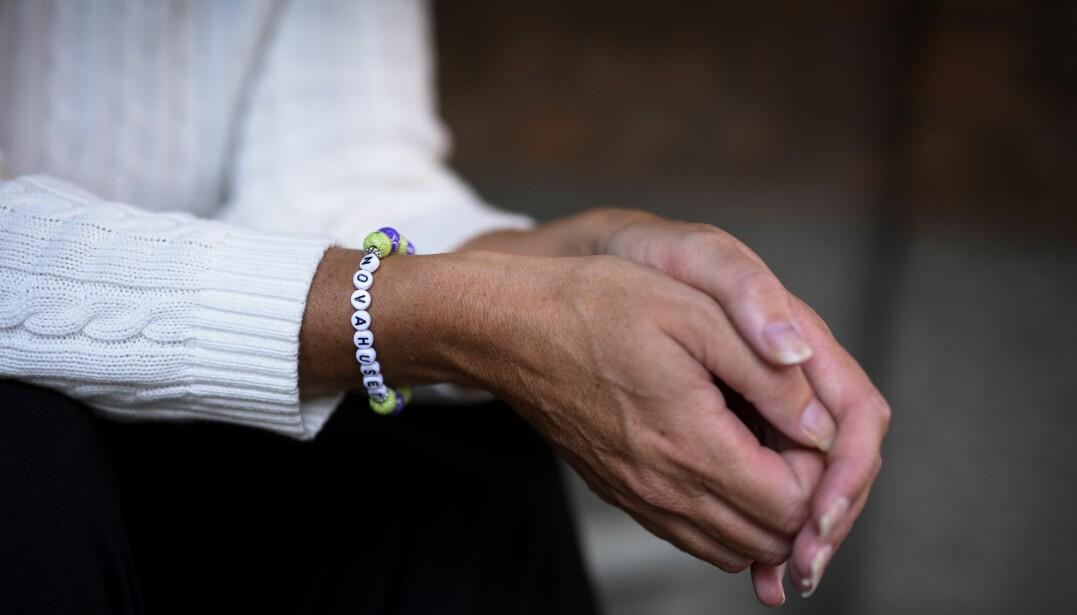 """Paulinas händer i närbild. Hon har en vit stickad tröja och runt ena handleden bär hon ett armband med pärlor som stavar ut """"Novahuset""""."""