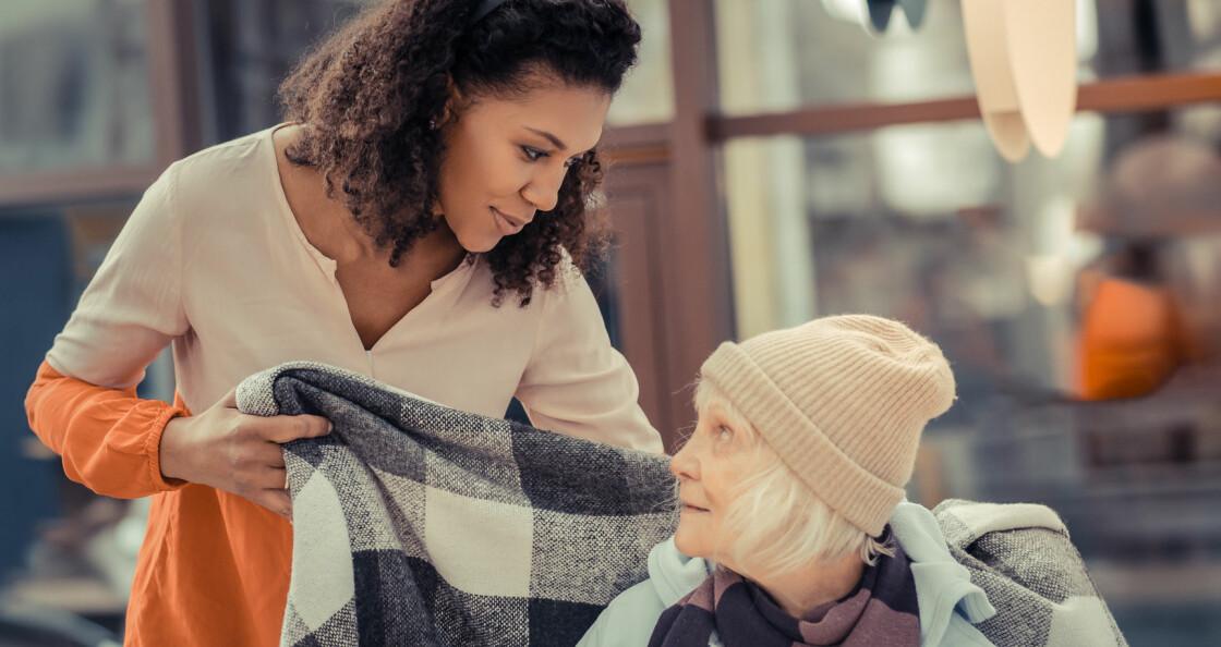 Ung kvinna lägger filt om äldre kvinnas axlar.