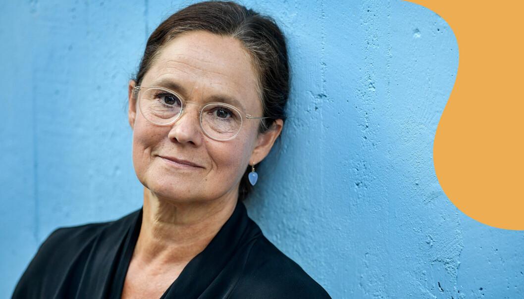 Pernilla August framför blå vägg tittar in i kameran