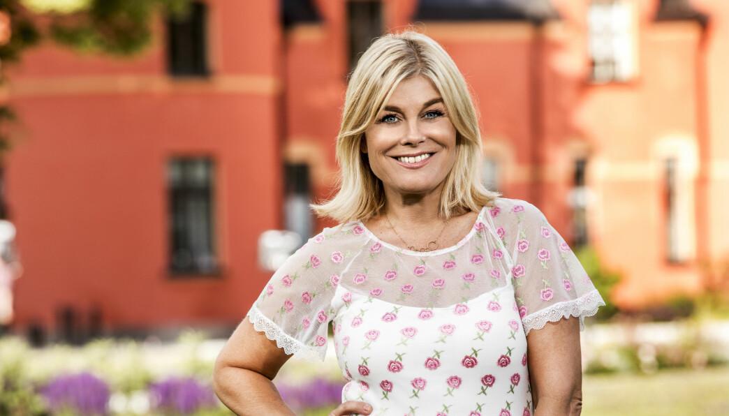 Pernilla Wallgren tittar leende in i kameran framför en röd byggnad. Solen skiner och bakom henne skymtar lila blommor.