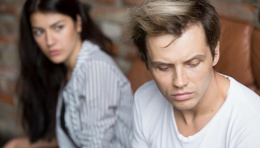 Grälande par sitter i en säng och ser ledsna och upprörda ut.