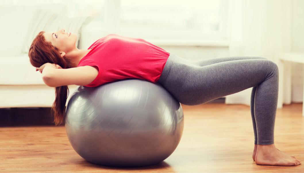 En kvinna övar på pilatesboll