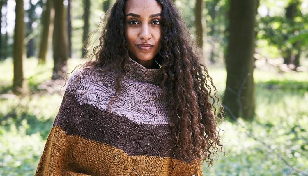 Porträtt av ung kvinna i en stickad poncho i tre olika färger