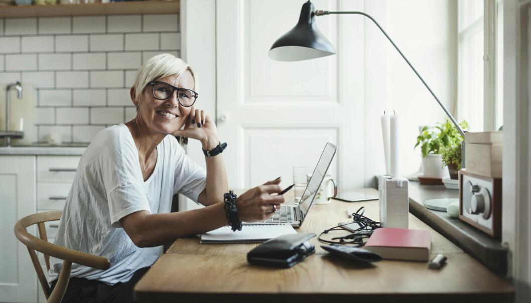 Porträtt av glad industridesigner vid skrivbord hemma.