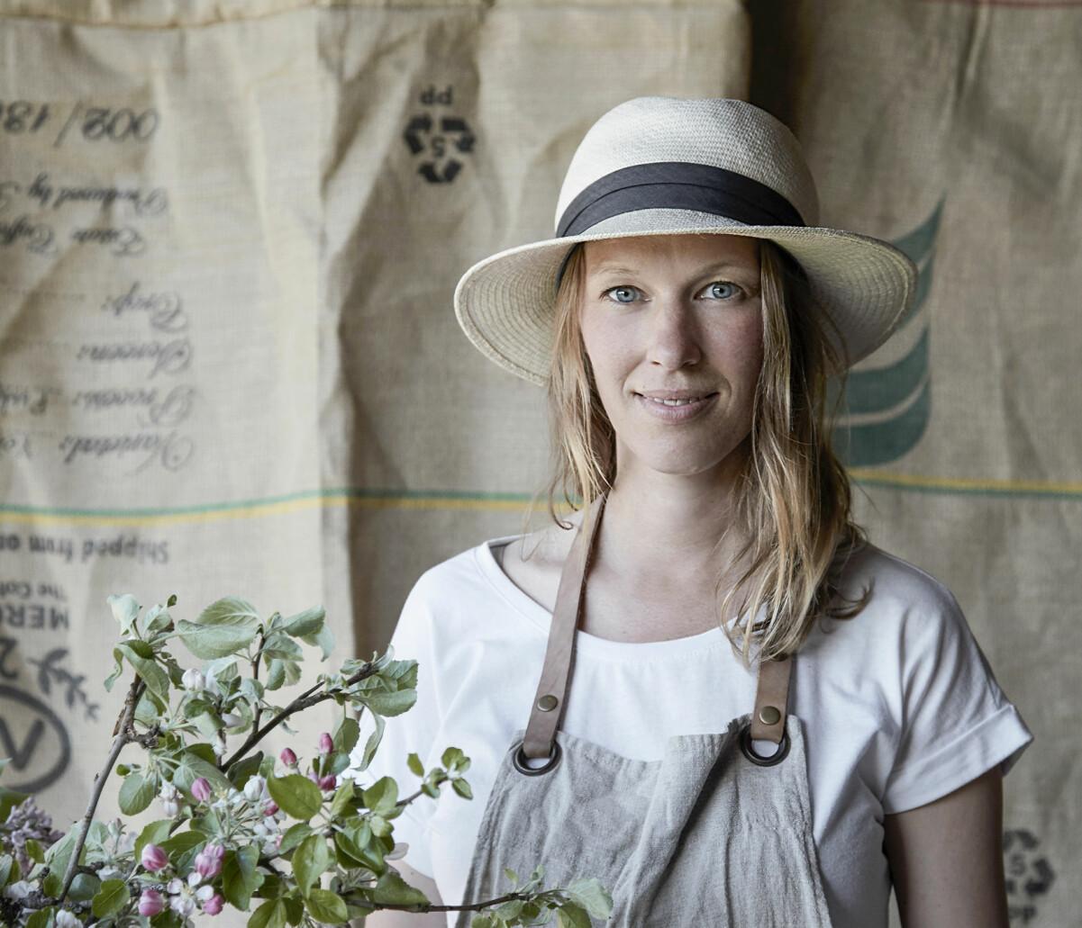 Porträtt av Maja i halmhatt och med en blomma.