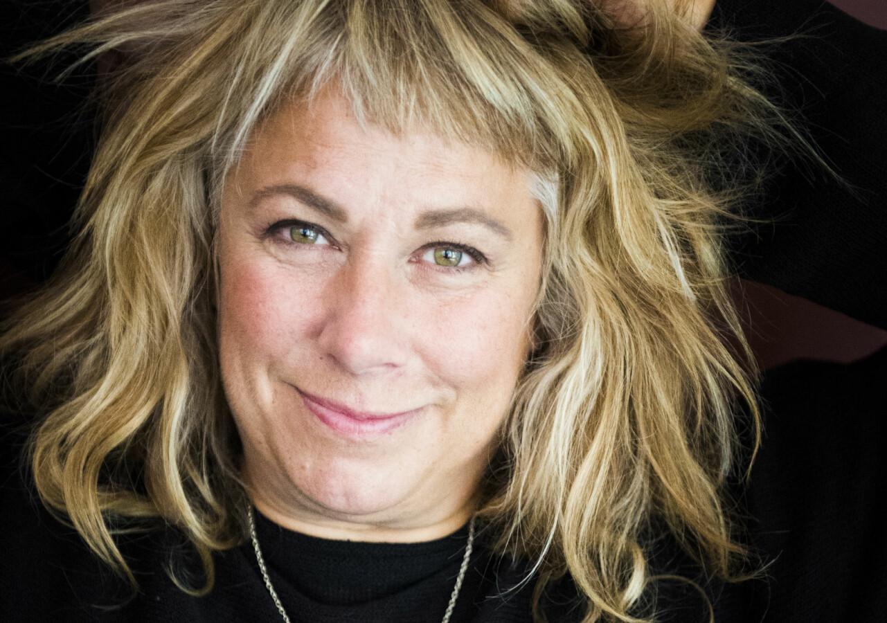 Porträtt av Stina Wollter som ligger ner med armarna över huvudet.