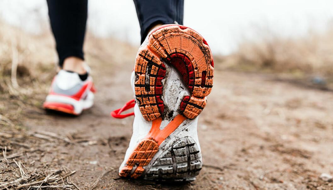 En kvinnas smutsiga träningsskor är i fokus när hon går på ern lerig väg.