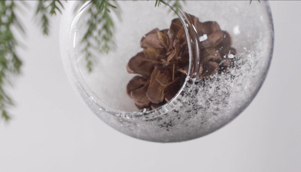 Julpyssel med julkula som dekoreras med självhäftande snö och juliga dekorationer som kottar, grankvistar eller figurer.
