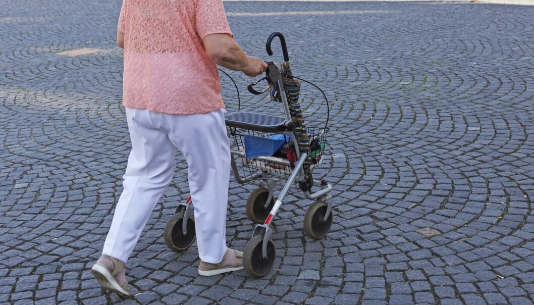 En äldre dam går utomhus med en rullator.