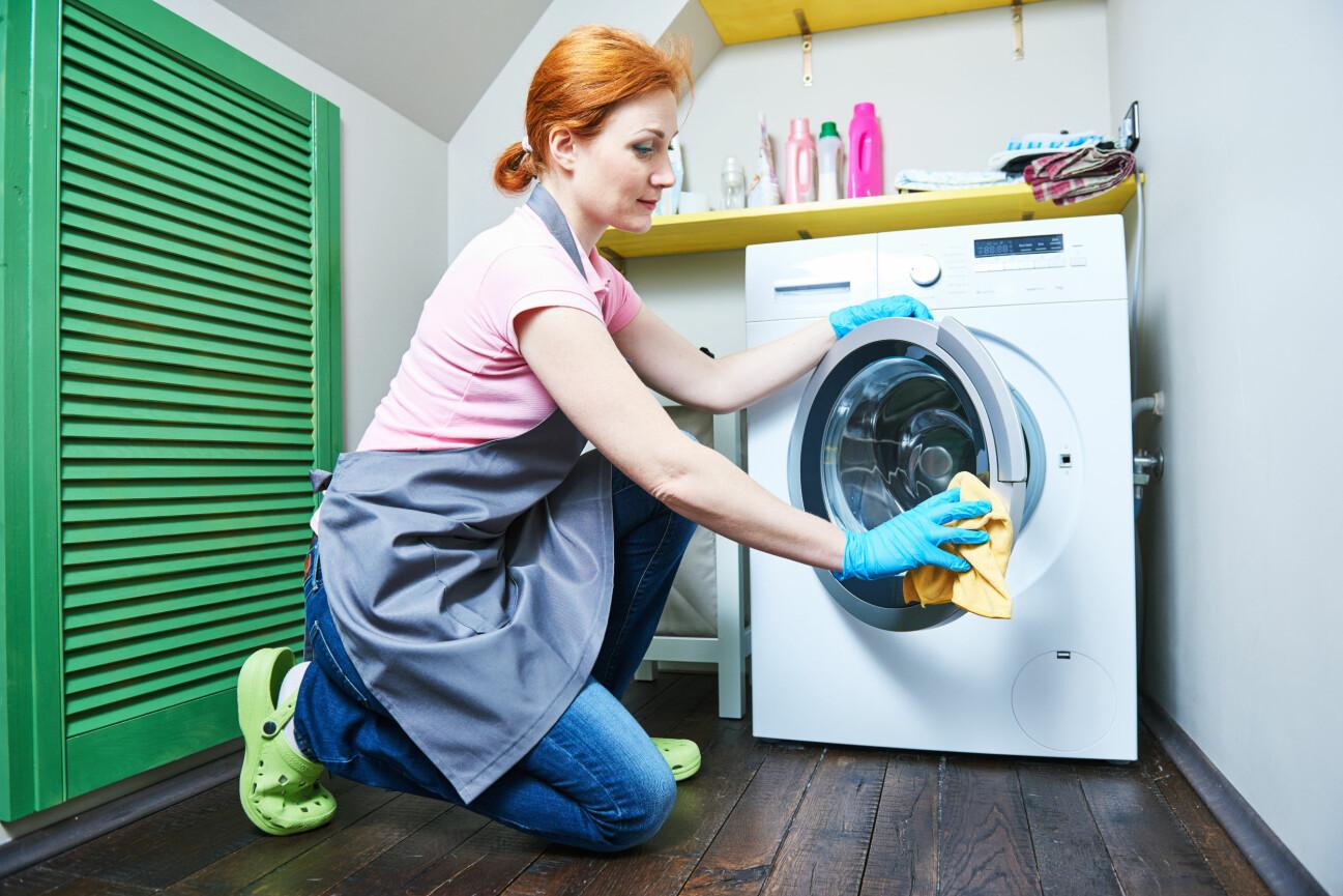 Kvinna rengör tvättmaskinens lucka.