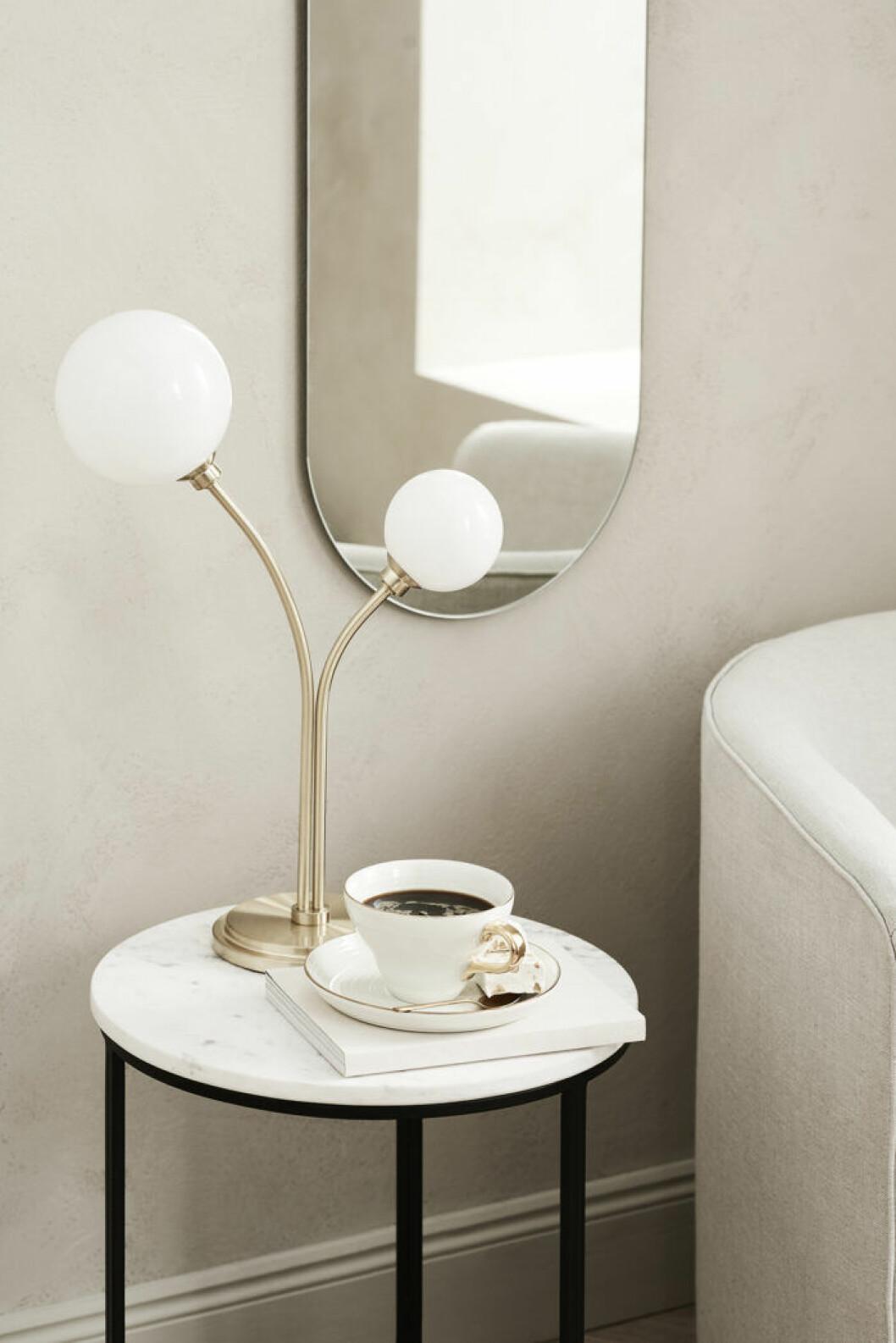 Retroglammig spegel och lampa till ett sovrum i hotellstil