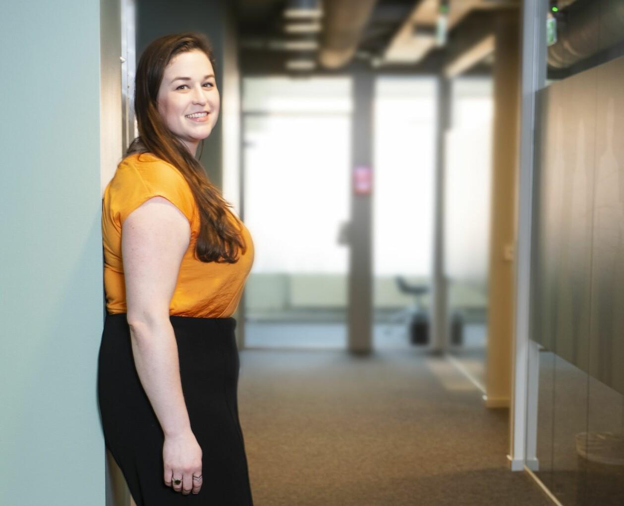 Ekonomen Sabrina Thams står lutad mot en vägg och ler.