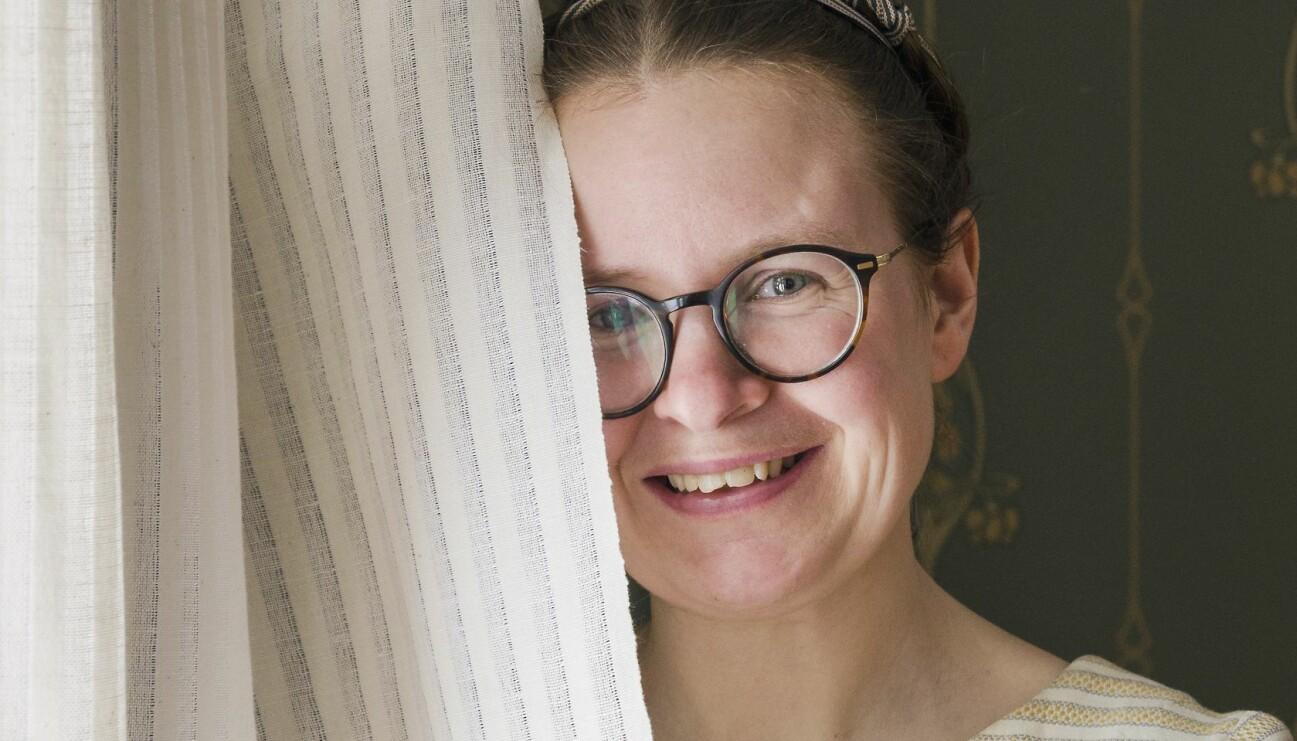 Sara Kånåhols har står framför ett fönster och håller sin egenvävda gardin framför halva ansiktet och berättar om sitt projekt att dokumentera ödehusgardiner.