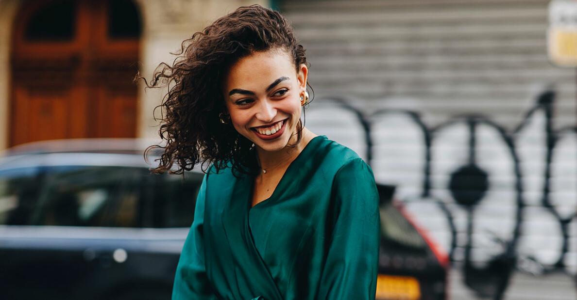 Kvinna i brunt lockigt hår ler stort