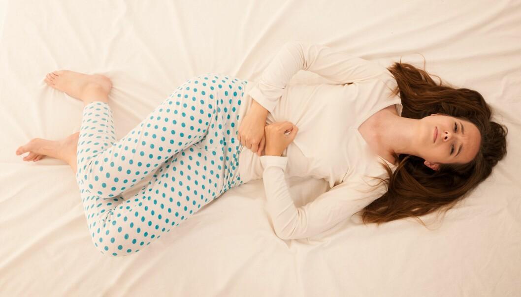 En kvinna ligger i en säng och håller sina händer på sin mage. Hon verkar lida av smärta. Kvinnan har långt brunt hår, en vit tröja och vita byxor med blåa prickar.