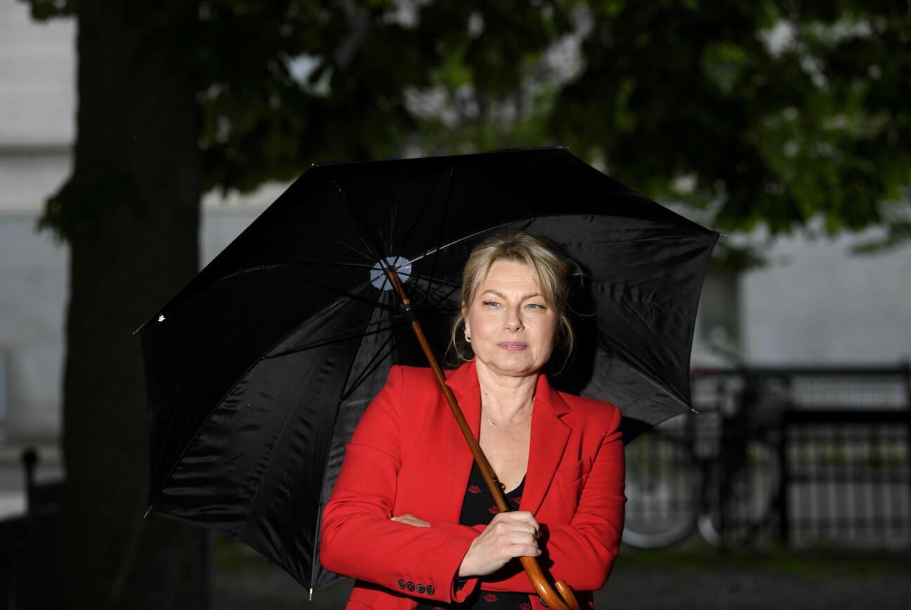 Helena Bergström håller ett paraply. Hon har en röd kavaj, blont hår i en hästsvans och blå ögon.