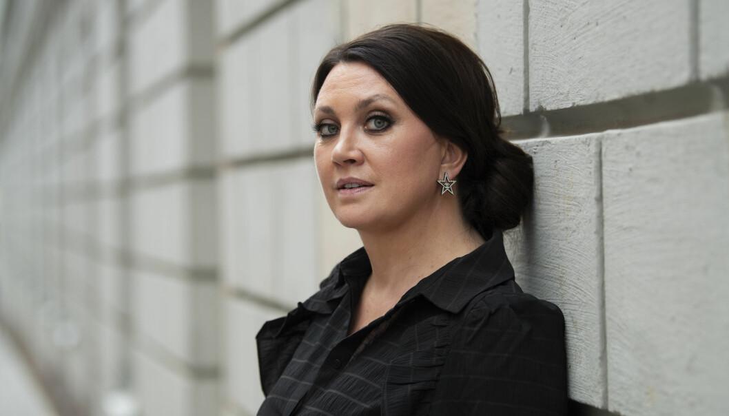 Porträttbild av Camilla Läckberg som står lutad mot en vägg och tittar in i kameran.a