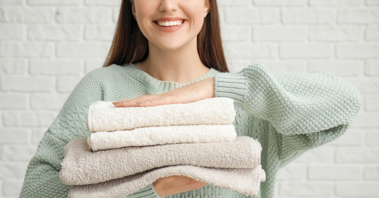 En kvinna som håller i en hög med handdukar som blivit rena tack vare ättika