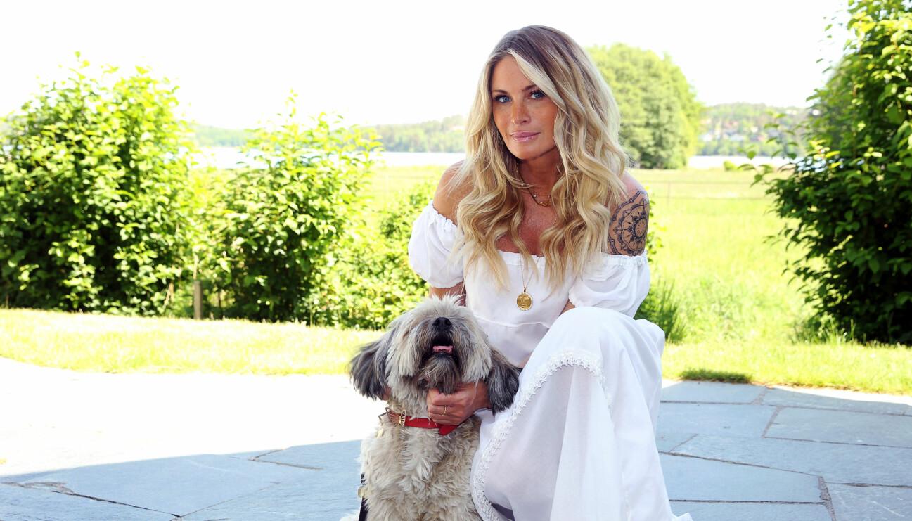 Carolina Gynning sitter ner bredvid sin hund. Carolina bär en vit klänning och har lång, blont hår.