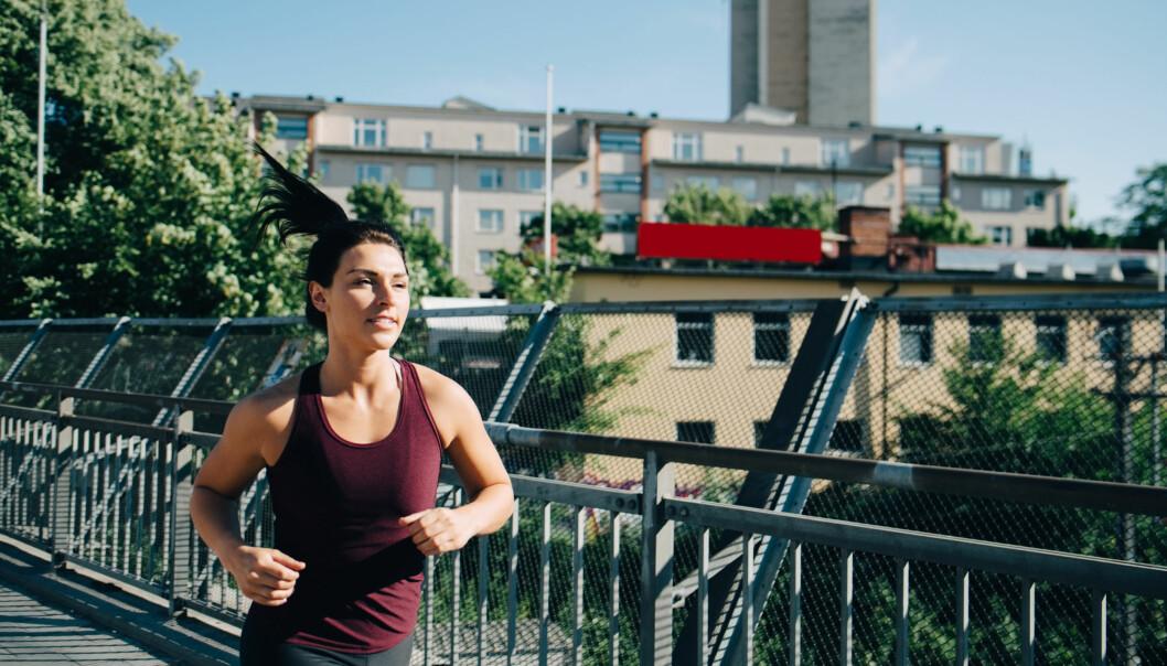 Kvinna joggar på bro i stad