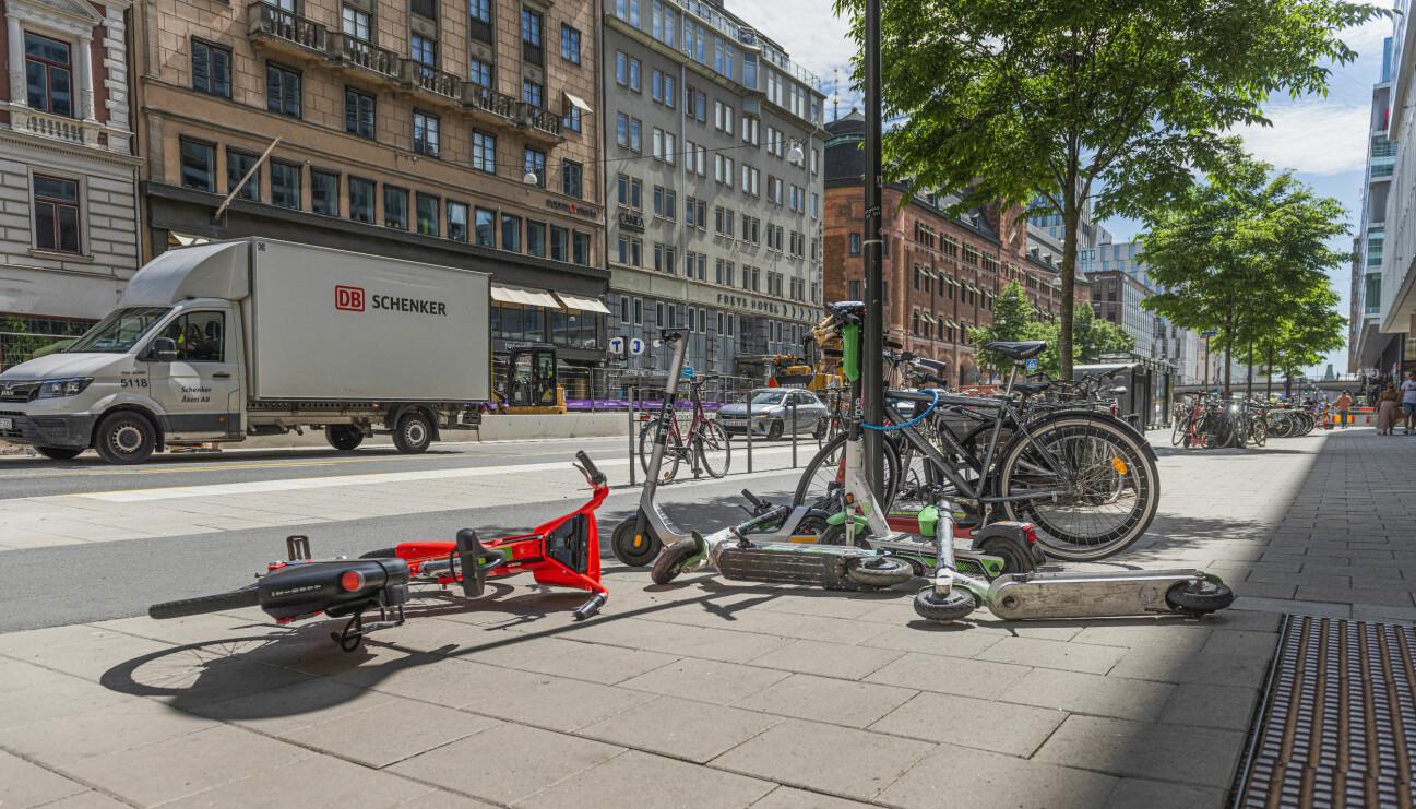 Elsparkcyklar och vanliga cyklar som ligger på gatan och trottoaren, slarvigt slängda.