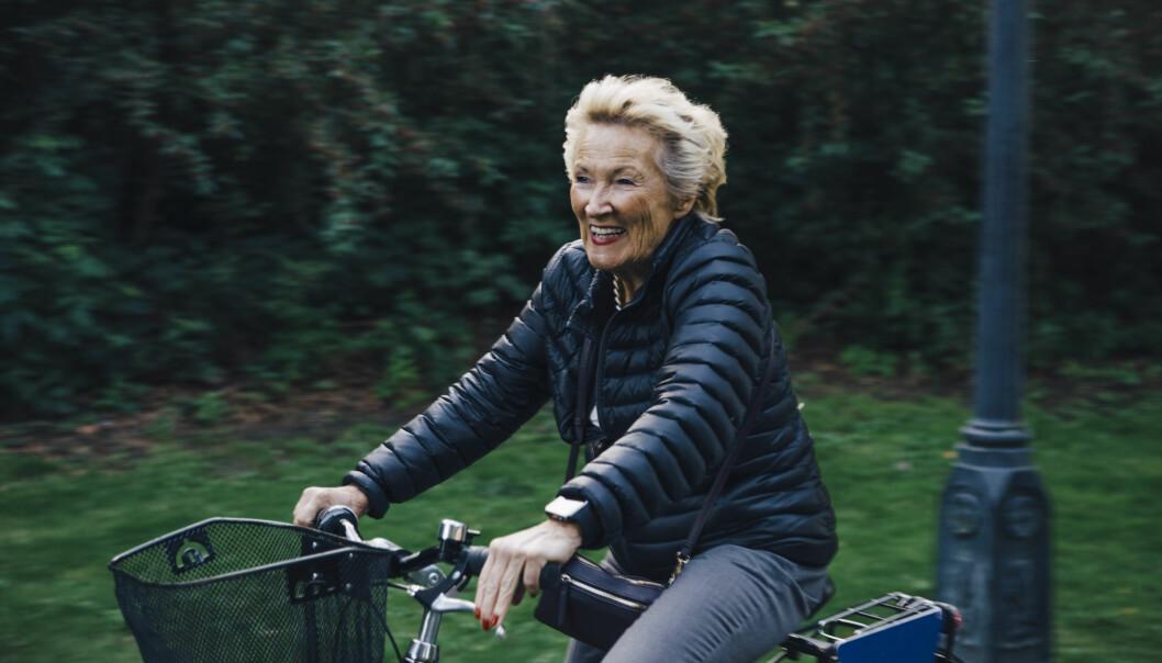 Leende äldre kvinna cyklar cykelväg