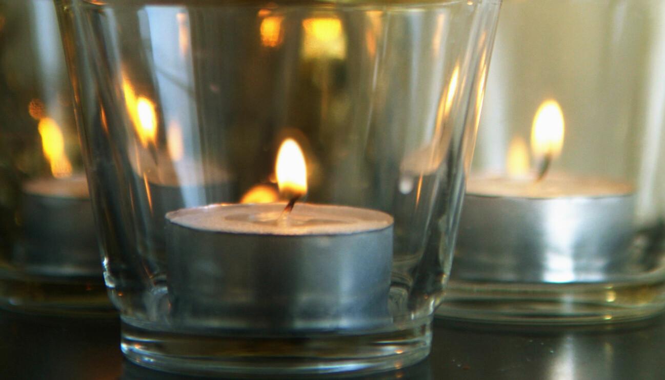 Ett värmeljus som brinner i en ljusbehållare.