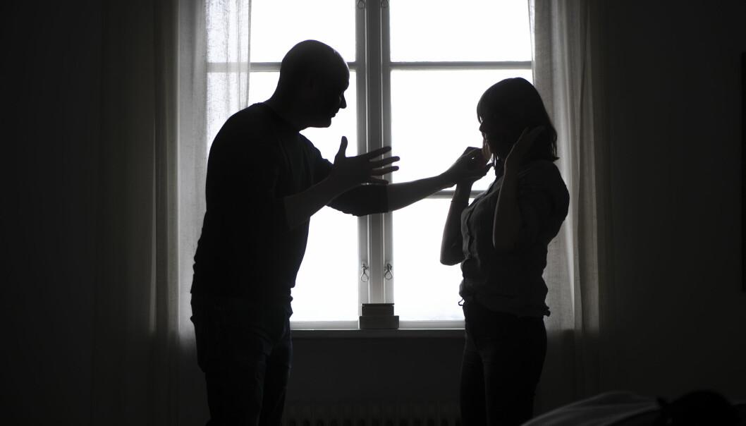 Siluetten av en man och en kvinna bråkar.