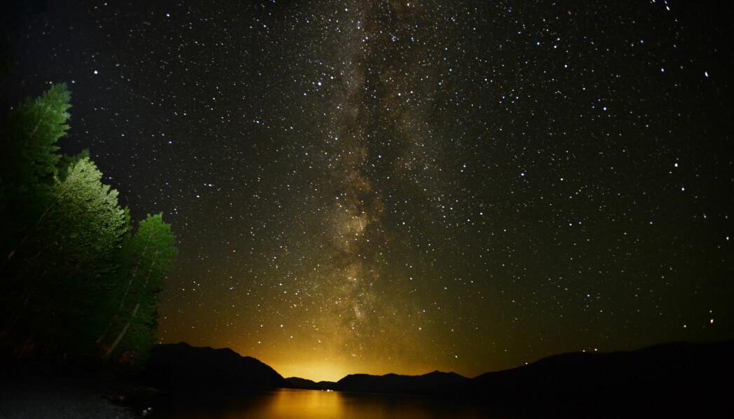 Vintergatan fotad över vatten och rester av en solnedgång