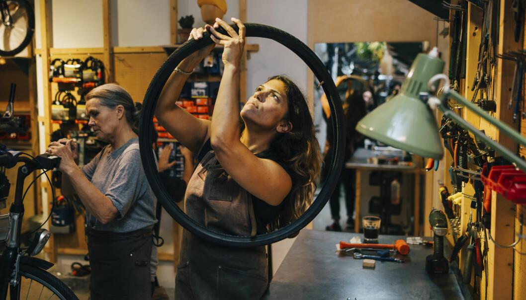 Kvinnliga kollegor lagar cykel i verkstad