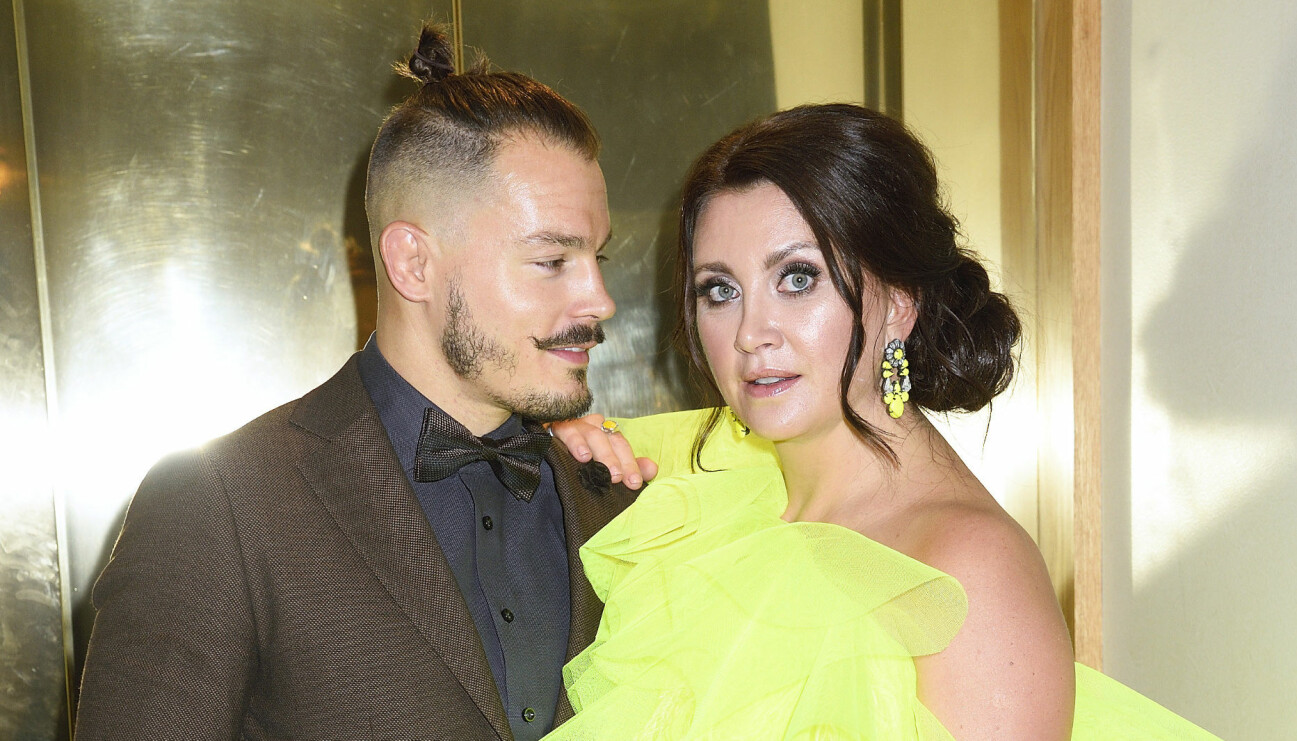 Simon Skölds och Camilla Läckberg står bredvid varandra. Simon bär en brun kostym och Camilla bär en neongul klänning.