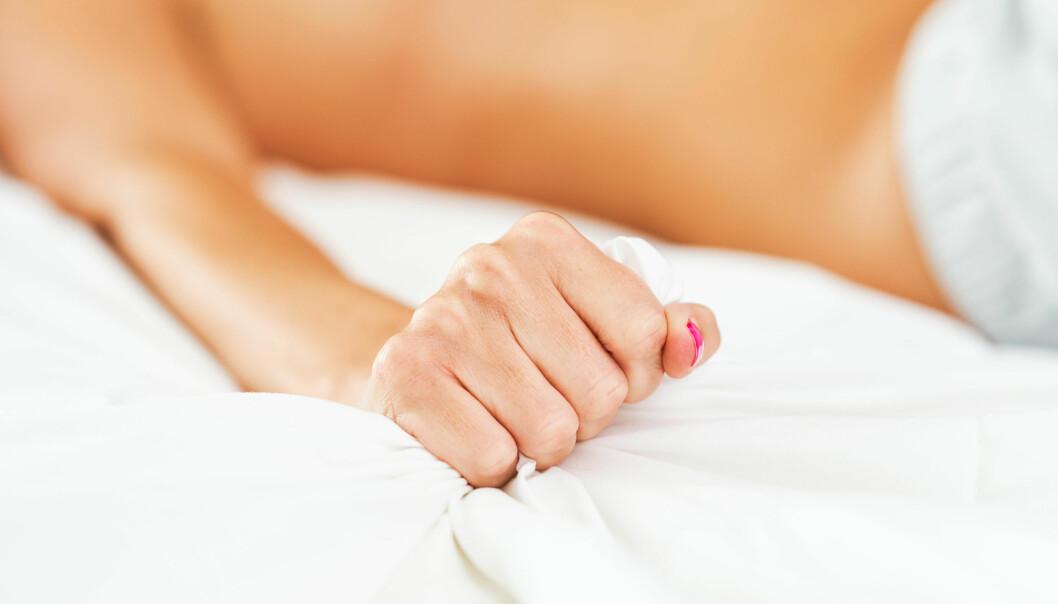 En hand med rosa naglar kramar om ett vitt lakan.