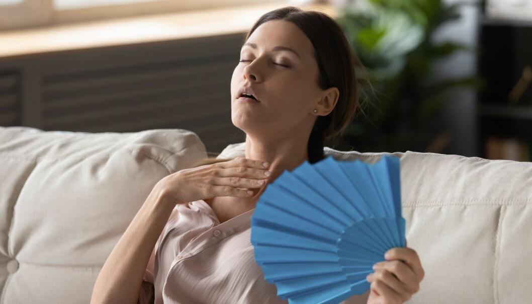 En ung kvinna sitter i en soffa och svalkar sig med en solfjäder.