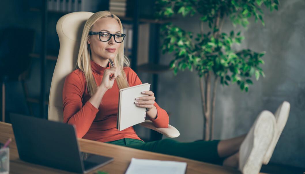 Kvinna i glasögon funderar. Håller ett block i handen vid skrivbord framför laptop.