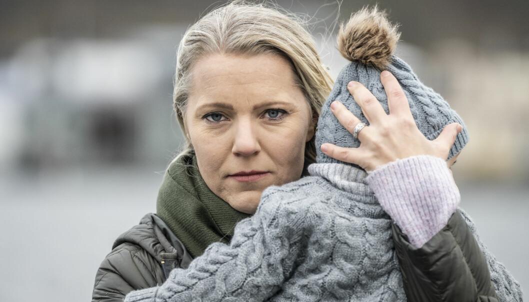 Porträttbild av Carina Bergfelt som tittar in i kameran, med sonen Hamilton i famnen, bortvänt från kameran.