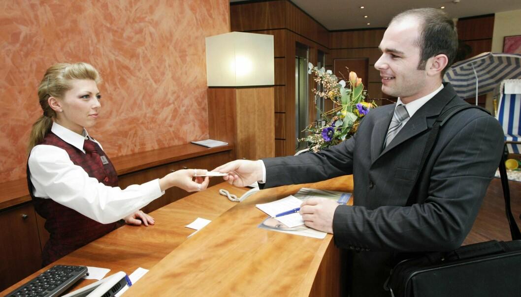 En kvinnlig receptionist ger en manlig hotellgäst sin rumsnyckel.
