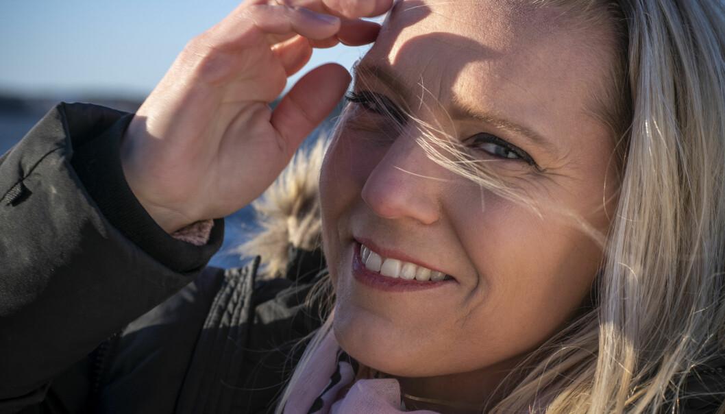 Närbild av Carina Bergfeldt som ler och håller undan håret från sitt ansikte. Bilden är tagen utomhus och det verkar blåsa.