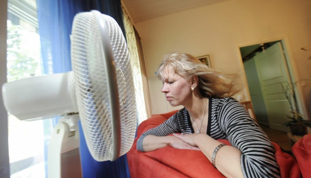 En kvinna med blont hår sitter framför fläkten och svalkar sig i sommarvärmen.