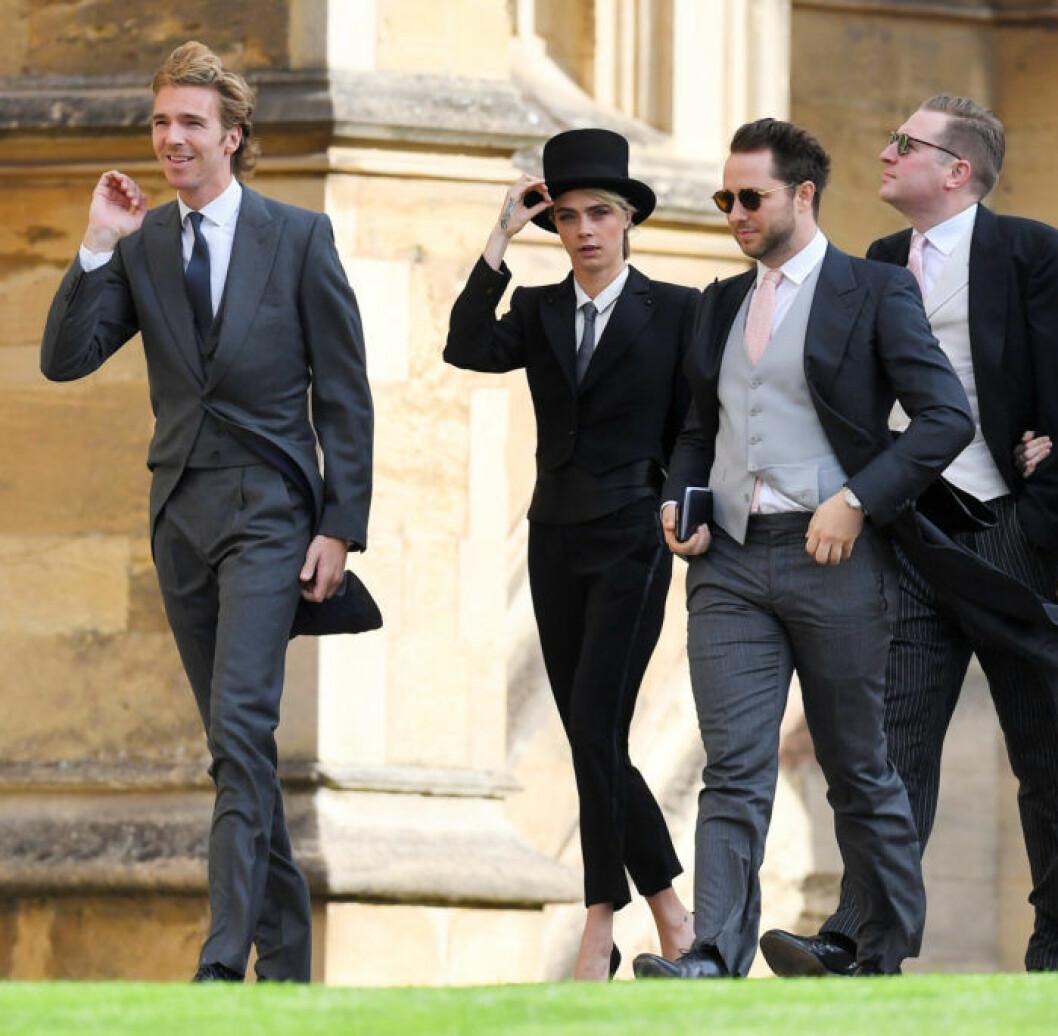 Cara Delevigne (mitten) bar svart kostym och hög hatt.