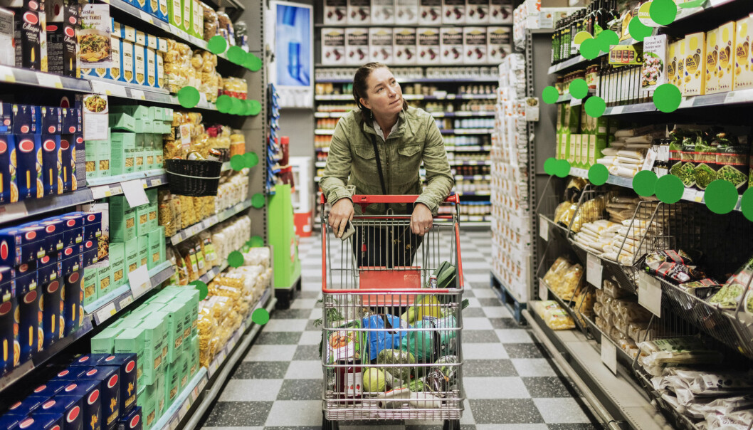 Kvinna lutar sig mot en kundvagn i en matvaruaffär.